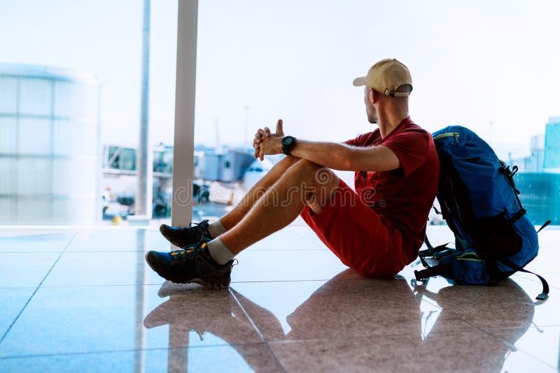 один путешественник-рюкзак, сидящий на аэродромном полу, глядя в окно зала и ожидая посадки на самолет стоковое изображение