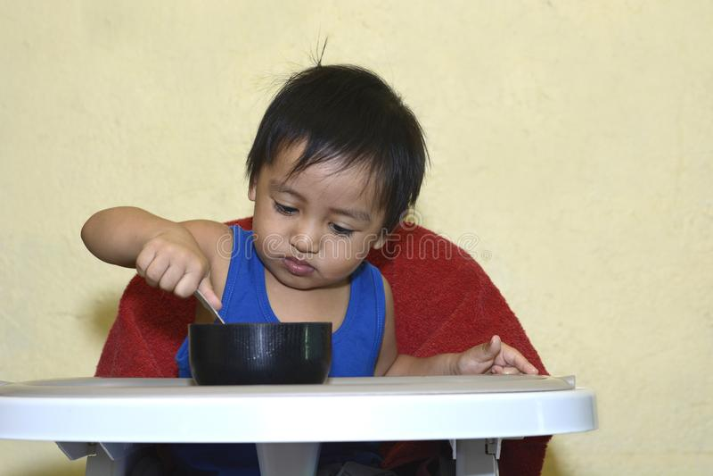 Один 1-ти летний азиатский ребёнок уча съесть самостоятельно, грязный на младенце обедая стул дома стоковые фотографии rf