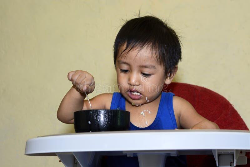 Один 1-ти летний азиатский ребёнок уча съесть самостоятельно, грязный на младенце обедая стул дома стоковые изображения