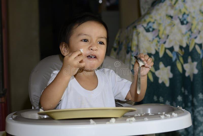 Один 1-ти летний азиатский ребёнок уча съесть самостоятельно ложкой, грязной на младенце обедая стул стоковое изображение rf