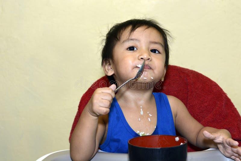 Один 1-ти летний азиатский ребёнок уча съесть самостоятельно ложкой, грязной на младенце обедая стул стоковое изображение