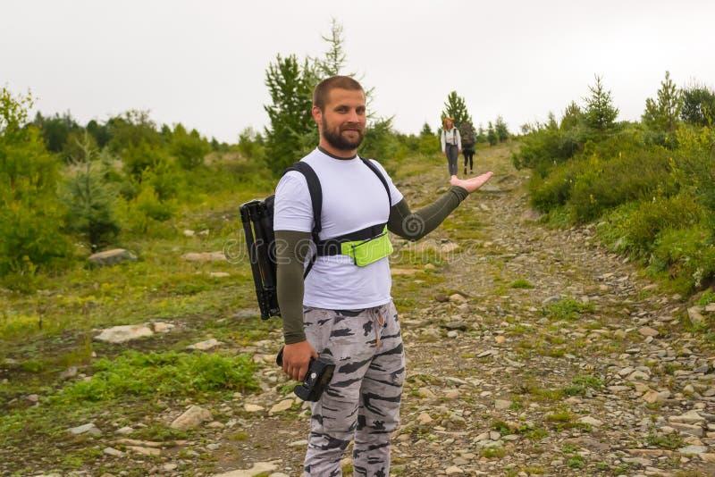 Один туристский парень держа дальше девушек руки 2 с goi рюкзаков стоковые фото