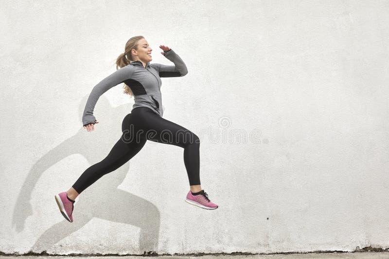 Один усмехаться молодой женщины счастливый, скачущ в средний-воздух, стоковая фотография
