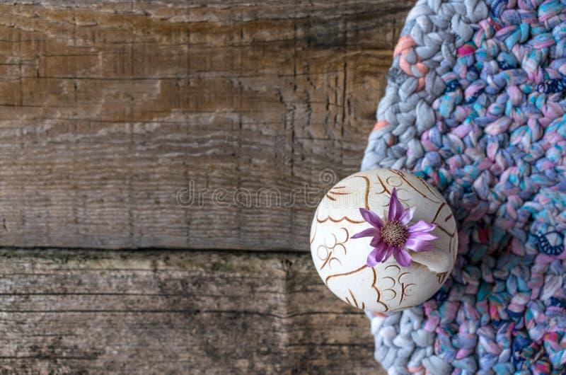 Один цветок Xeranthemum сирени на круглой вазе глины на связанной заплате стоковое фото rf