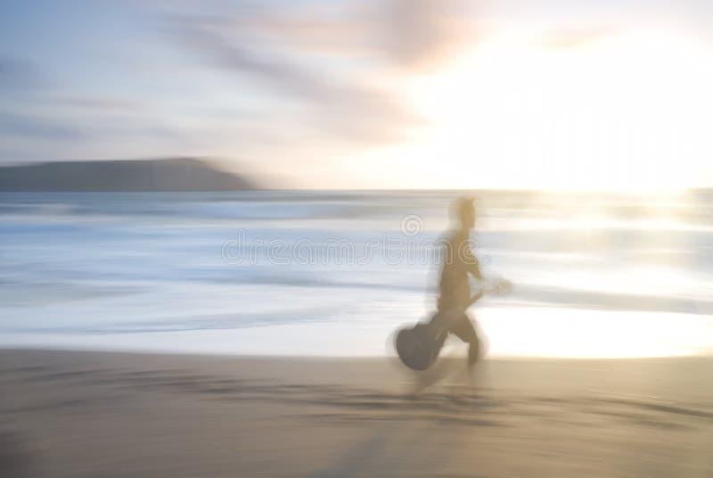 Один человек гуляя на пляж с гитарой. стоковое фото rf