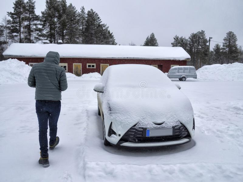 Один человек идя рядом с автомобилем покрытым снегом стоковые фото
