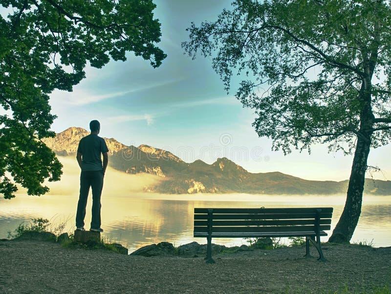 Один человек сидит на стенде около лазурного озера горы человек ослабляет стоковые изображения rf