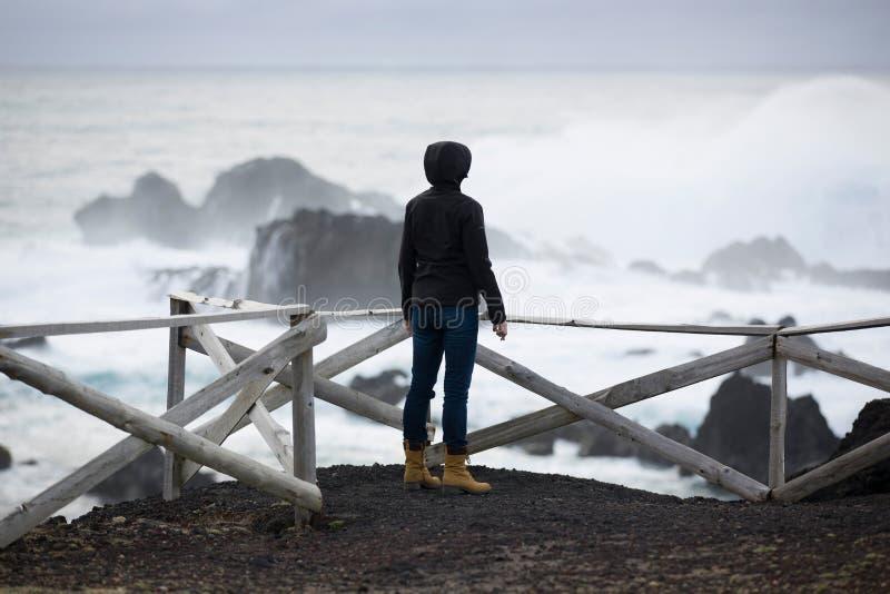 Одичалый, штормовая погода, weavy океан, скалистый берег, деревянная загородка, женщина в черном взгляде на море стоковые фото