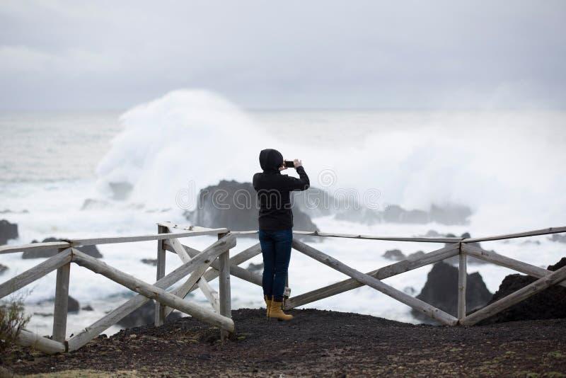 Одичалый, штормовая погода, weavy океан, скалистый берег, деревянная загородка, женщина в черном взгляде на море стоковое изображение