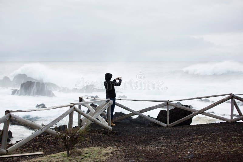 Одичалый, штормовая погода, weavy океан, скалистый берег, деревянная загородка, женщина в черном взгляде на море стоковая фотография