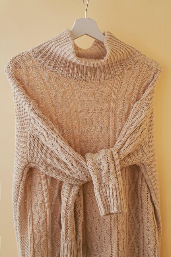Одна бежевая пастель вяжет теплый свитер с завязанными рукавами на вешалке стоковые фотографии rf