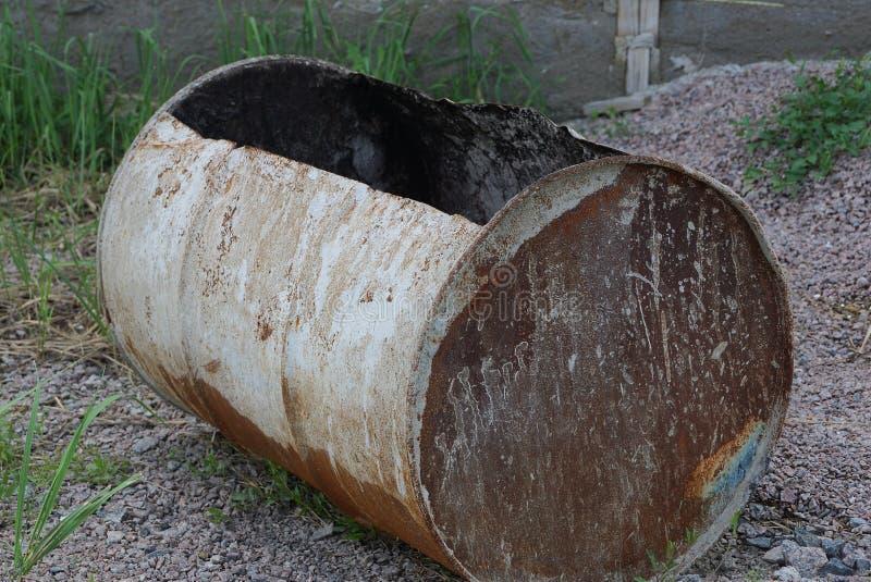 Одна большая ржавая старая и грязная ложь бочонка на том основании стоковые фото