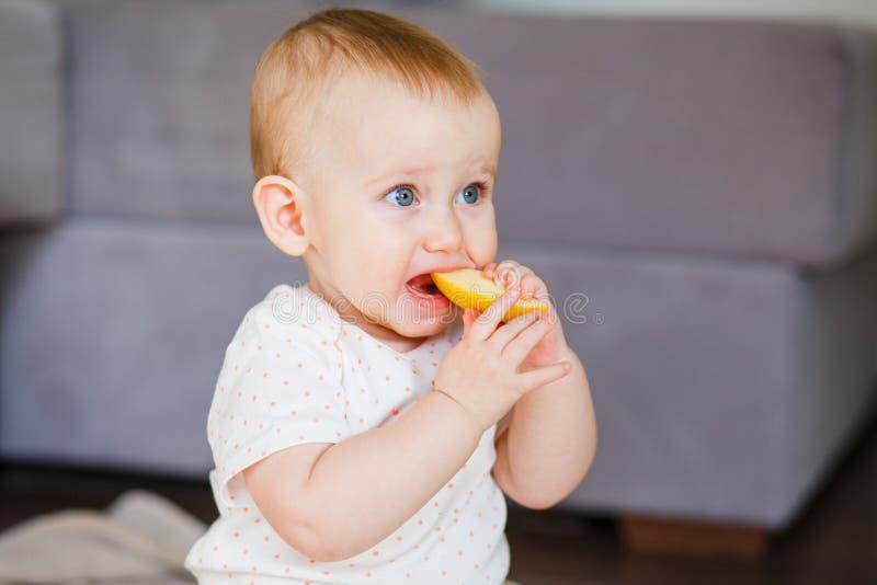 Одна девушка года пробует сдержать часть желтого яблока Еда для концепции детей стоковые фотографии rf