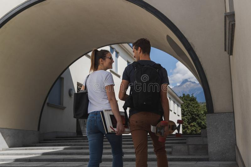 Одна девушка с сумкой и книгами и одним мальчиком с рюкзаком и коньком идя в школу после летних отпусков стоковые фото