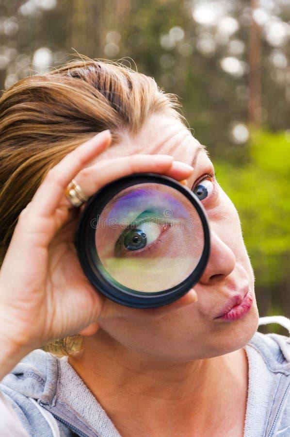 Одна женщина глаза наблюдая через увеличивая объектив стоковое изображение