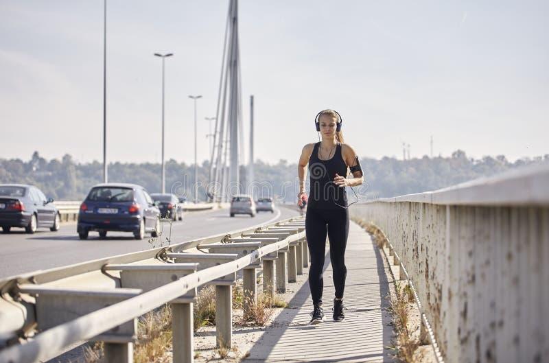 Одна молодая женщина, бежать jogging на мосте, автомобилях в предпосылке, слушая музыку на наушниках стоковое изображение