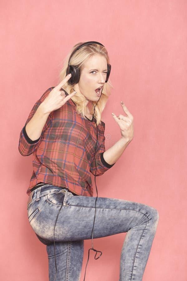 Одна молодая женщина утеса, показывая жестами с ее рок-музыкой пальцев, пока слушающ оно на наушниках, стоковое изображение rf