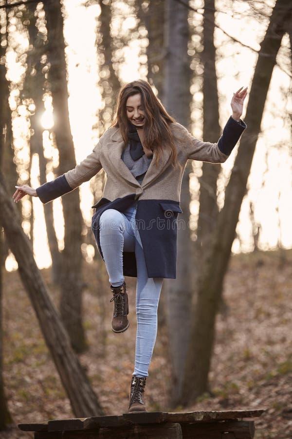 Одна молодая милая девушка, стоя на таблице при одна нога, находя баланс, стоковое фото