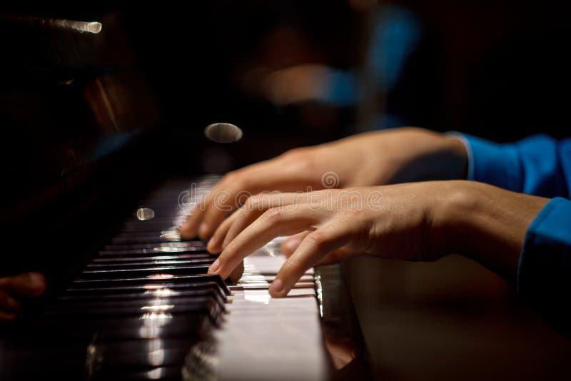 Одна мужская рука на рояле Ладонь лежит на ключах и играет аппаратуру клавиатуры в музыкальной школе студент учит к стоковое фото rf