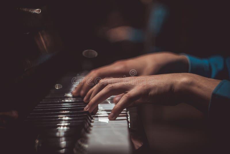 Одна мужская рука на рояле Ладонь лежит на ключах и играет аппаратуру клавиатуры в музыкальной школе студент учит к стоковые изображения