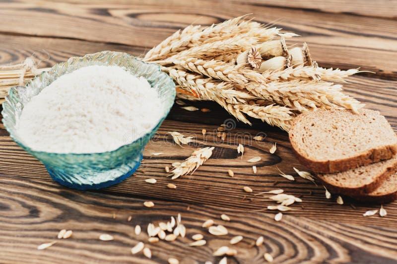 Одна пачка пшеницы и мака и серия разбросанного зерна и 3 куска хлеба и муки в стеклянном шаре на старом деревянном pl стоковое фото
