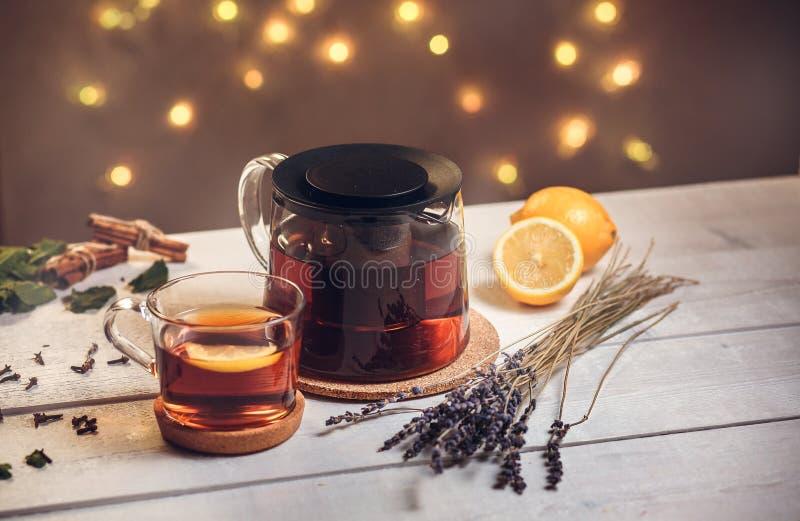 Одна полная чашка черного чая с лимоном и чайником стоковое изображение