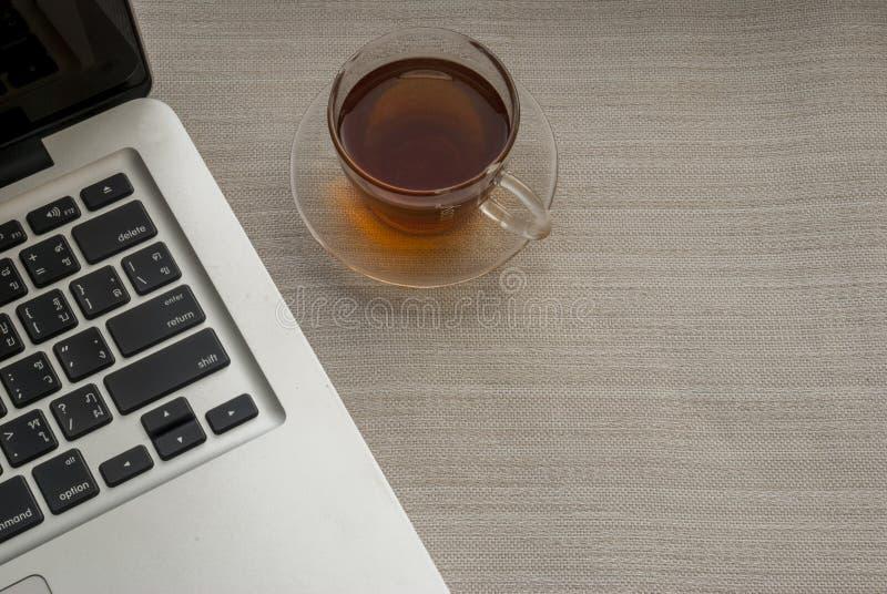 Одна чашка чаю на правильной стороне ноутбука стоковое изображение