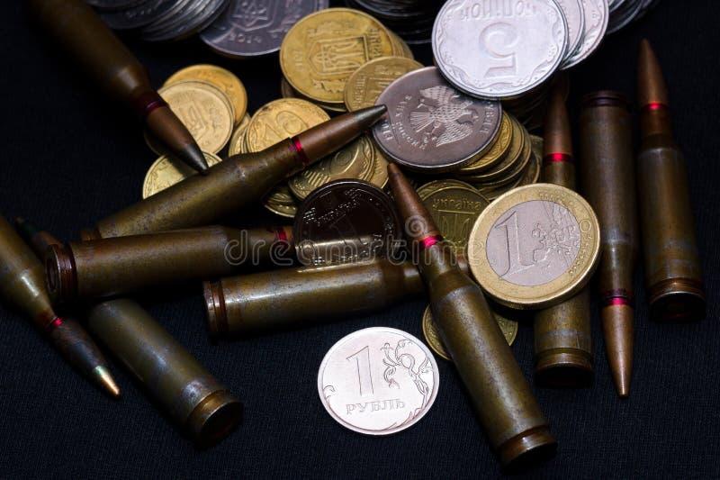 Одно евро, русский рубль и малые украинские монетки с боеприпасами винтовки воинскими на черной предпосылке Символизирует войну д стоковое фото rf