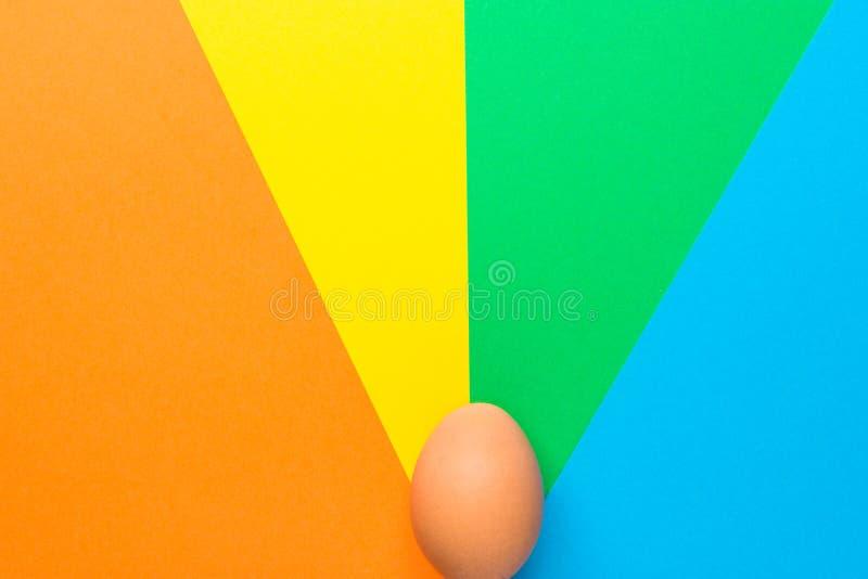 Одно коричневое пасхальное яйцо на пестротканом луче pinwheel разрывало предпосылку в ретро эстетике 60s Творческий плакат праздн стоковое изображение