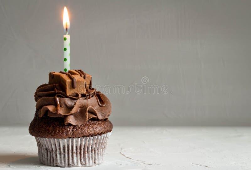 Одно пирожное карамельки шоколада с освещенной свечой на темном сером backg стоковые фотографии rf