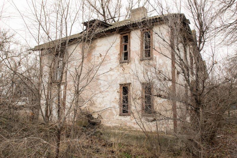 Одно фото старого и ужасного покинутого сельского дома, который окончательно ухудшает, перерастанное с старыми деревьями Здесь жи стоковая фотография
