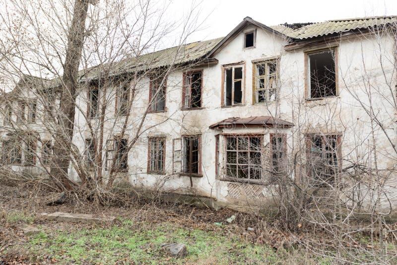 Одно фото старого и ужасного покинутого сельского дома, который окончательно ухудшает, перерастанное с старыми деревьями Здесь жи стоковое изображение rf