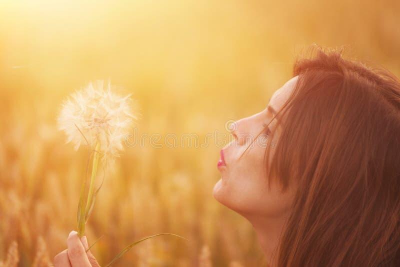 Одуванчик молодой женщины дуя в ландшафте осени на заходе солнца стоковые фотографии rf