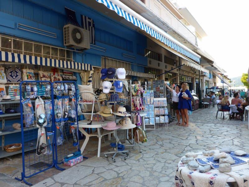 7-ое августа 2018 Туристы выбирают сувениры в сувенирном магазине в одной из улиц городка Vathi прописное и основной стоковое изображение