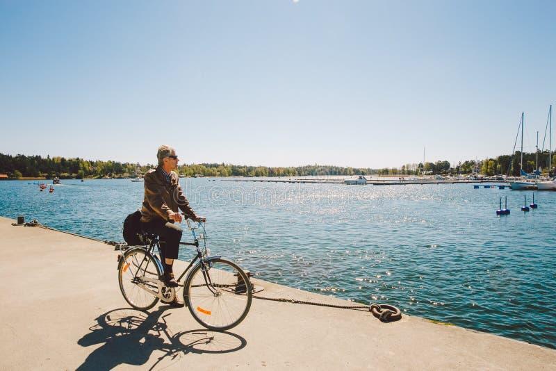 17-ое апреля 2014 Город nynashamn в Швеции Обваловка Балтийского моря Койка, автостоянка и шлюпки, корабли Человек на bic стоковые фото