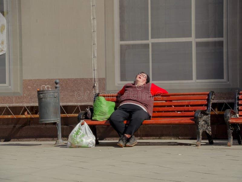 30-ое апреля 2017, Россия, Москва Бездомный человек спит на стенде стоковая фотография rf