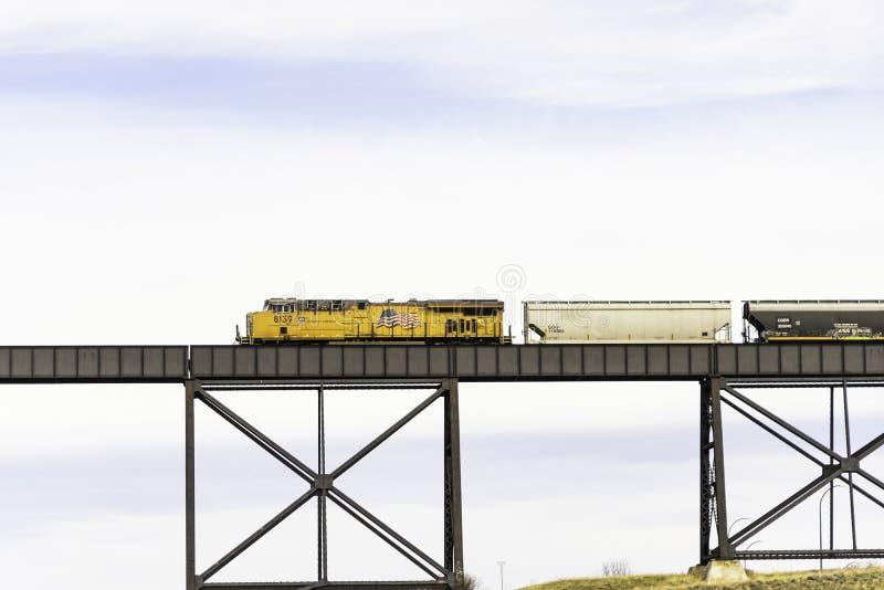 7-ое апреля 2019 - Lethbridge, Альберта Канада - канадский Тихий океан железнодорожный поезд пересекая высоководный мост стоковое фото rf