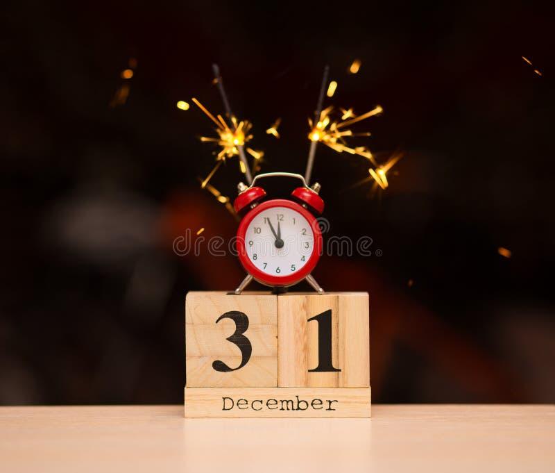 31-ое декабря установил на деревянный календарь с красным будильником на темной blured предпосылке стоковые фотографии rf