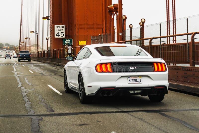 4-ое июля 2019 Сан-Франциско/CA/США - белый мустанг Форда GT путешествуя на мосте золотых ворот; вид сзади стоковые изображения rf