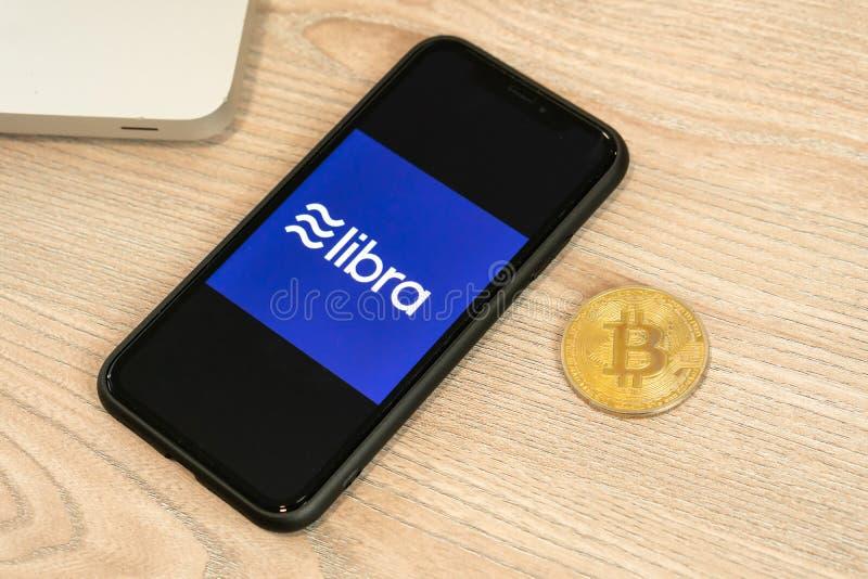 18-ое июня 2019, Любляна Словения - смартфон с логотипом Libra на ем, рядом с монеткой Bitcoin Глобальное Facebook новое стоковое фото rf