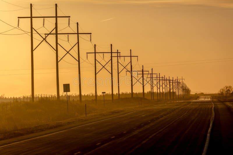 8-ое марта 2017, НЕБРАСКА - заход солнца над сельской проселочной дорогой фермы при грузовой пикап управляя строкой powerlines стоковое изображение rf