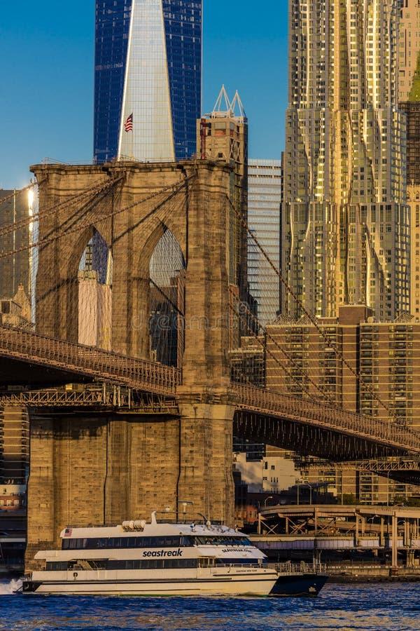 24-ое октября 2016 - НЬЮ-ЙОРК - Бруклинский мост и характеристики горизонта Манхаттана один всемирный торговый центр на восходе с стоковое фото rf