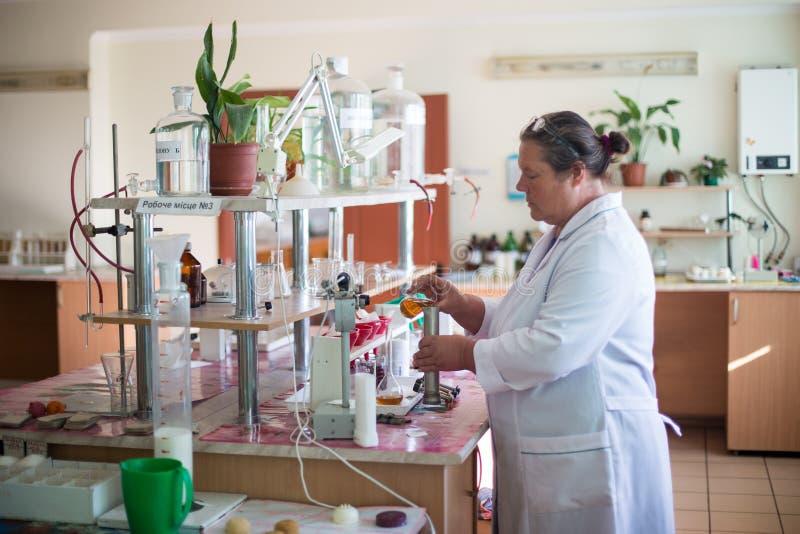 14-ое октября 2014 r Kyiv Кавказская средн-достигшая возраста женщина в белом пальто в химической лаборатории Специалист на работ стоковое фото