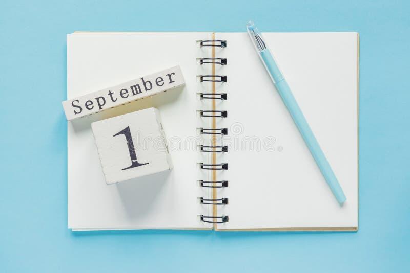 1-ое сентября на деревянном календаре на учебнике исследования на голубой предпосылке r стоковые фото