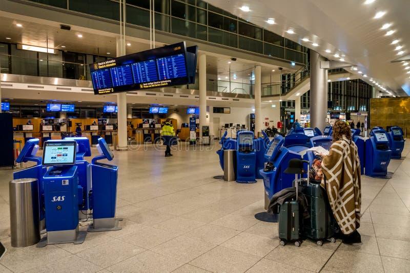 18-ое февраля 2019 Аэропорт Дания Копенгаген Kastrup Женщина подпирает непознаваемое с большим багажем чемоданов независимо стоковые фото