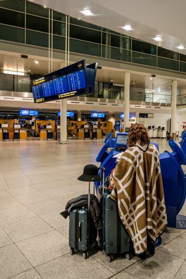 18-ое февраля 2019 Аэропорт Дания Копенгаген Kastrup Женщина подпирает непознаваемое с большим багажем чемоданов независимо стоковая фотография rf