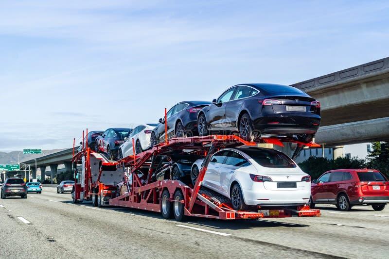 19-ое января 2019 Сан Bruno/CA/США - транспортер автомобиля носит корабли модели 3 Tesla новые вдоль шоссе в San Francisco Bay стоковое фото