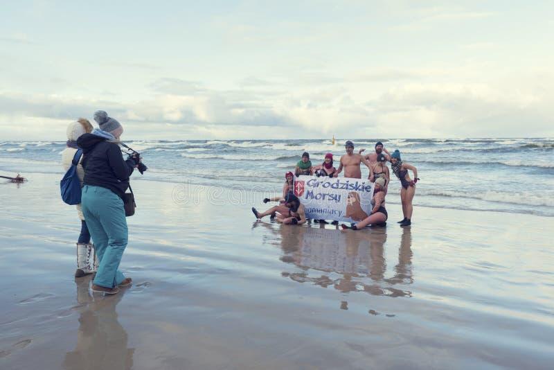 5-ое января 2019, Stegna, Польша Много людей фотографируя с плакатом во время плавания зимы в море стоковая фотография