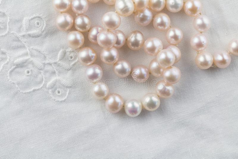 Ожерелье жемчуга на белой вышитой предпосылке белья - взгляде сверху строки розовых жемчугов стоковая фотография rf
