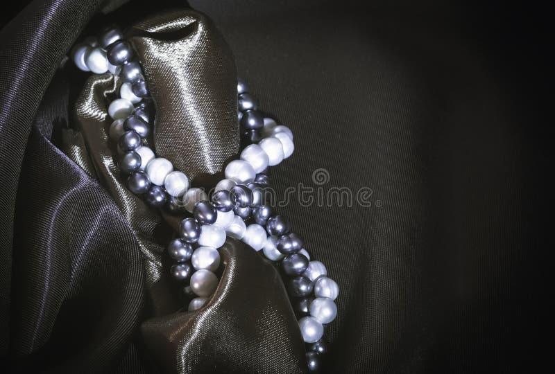 Ожерелья естественного жемчуга на темной Silk предпосылке стоковые фотографии rf